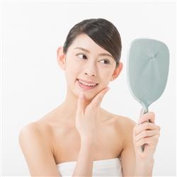 鏡をみて肌をチェックしてる女性
