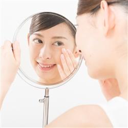 鏡をみて肌に触れている女性